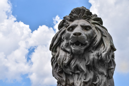 Close-up of a lions head statue on a cloudy background