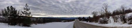 Panoramic view of a winter road with snow and dramatic clouds, and a mountain range in the background Stock Photo