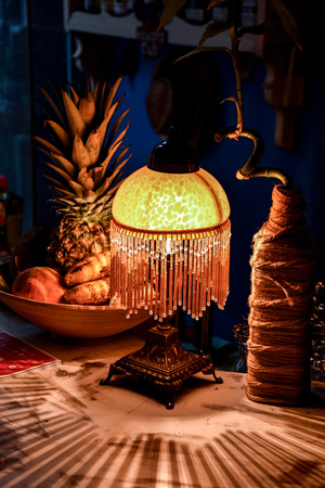 Organic looking lamp, fruits and a bottle-vase on a bar