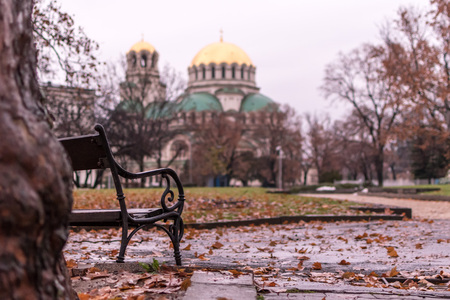 Nostalgic autumn view with a benach and the Alexander Nevsky Orthodox Christian Cathedral in Sofia, Bulgaria, in the background Stock Photo