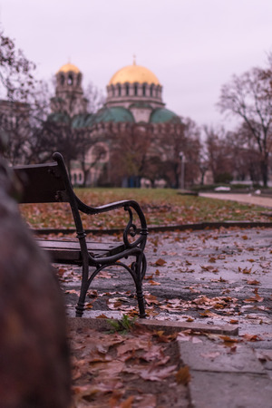 Nostalgic autumn view with a bench and the Alexander Nevsky Orthodox Christian Cathedral in Sofia, Bulgaria, in the background Stock Photo
