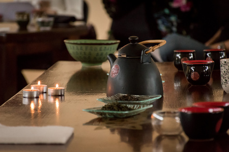 Preparation of chinese tea - table set with a kettle, cups, candles, and some green and black tea waiting to be done