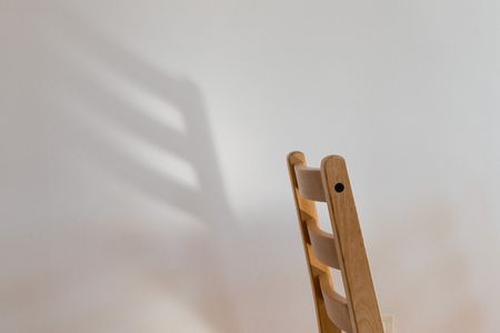 Chair dreaming of wings; the back of a wooden chair casts a wing-shaped shadow on a clean white wall behind it
