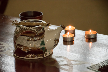 Preparation of chinese green and black tea - table set with a kettle, cups, candles