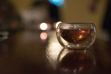 Transparent small glass of Chinese black tea on a table, shot contre-jour to candlelight Stock Photo