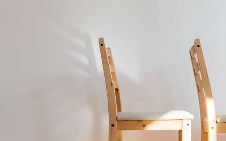 Chair dreaming of wings; two wooden chairs before a clean white wall, the back of one of casts a wing-shaped shadow