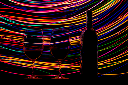 trails: Glasses and wine bottle on black background and trails