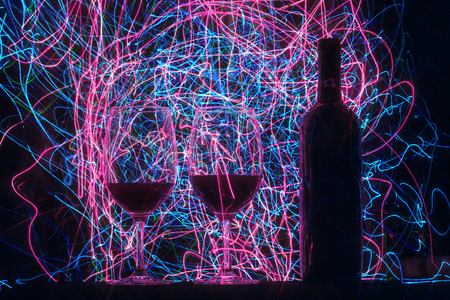 Glasses and wine bottle on black background and trails