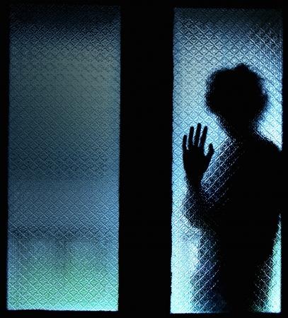 asustado: Muchacho asustado detr�s de la puerta de cristal que muestra un lado