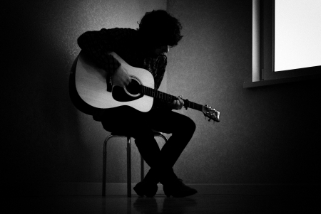 the stool: Man sitting on stool in dark room playing guitar Stock Photo