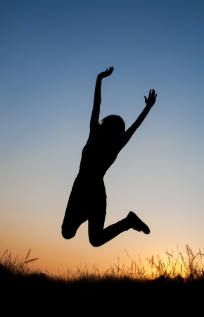 Silhouette of girl jumping in field photo