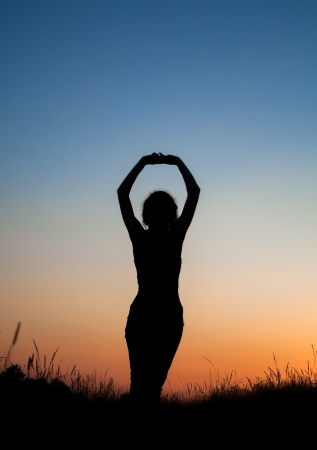 Silhouette of girl stretching herslef in field photo