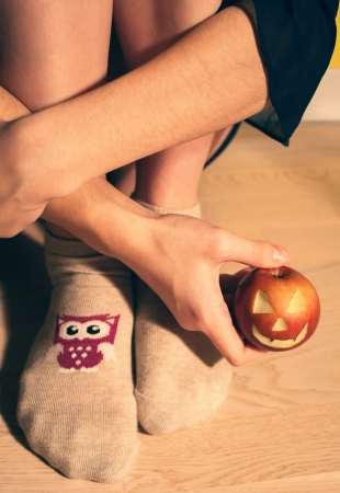 Woman sitting on floor with apple jack o lantern, vintage photo
