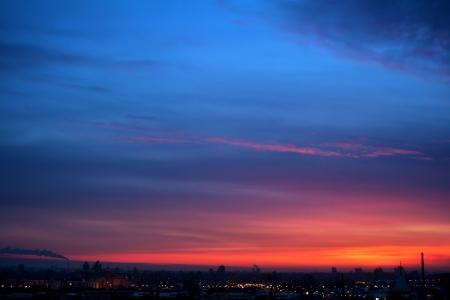noche: Cloudscape dramático en la noche azul de la ciudad y el cielo rojo