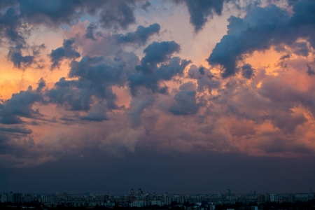 Dramatic evening cloudscape in city, orange overcast sky photo