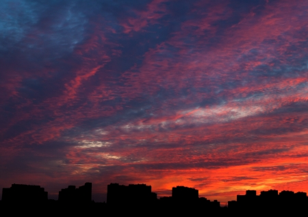 Dramatic evening cloudscape in city with silhouettes of buildings photo