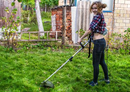 workwoman: Woman in Plaid Shirt Mowing Lawn Stock Photo