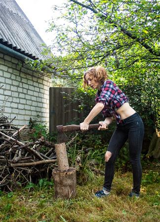 workwoman: Serious Woman Chopping Wood Stock Photo