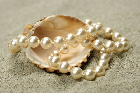 Sea shell with pearls on the sand