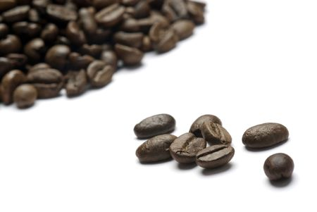 coffee crop: Coffee beans spilled onto a white background. Closeup of whole beans isolated on white.  Stock Photo