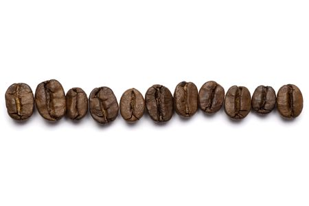 Coffee beans spilled onto a white background.  免版税图像