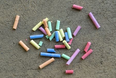 Multicolored chalks on the concrete sidewalk