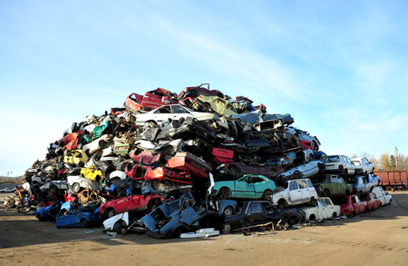 Old damaged cars on the junkyard waiting for recycling 免版税图像