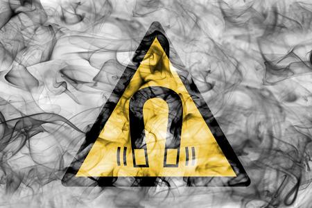Magnetic field hazard warning smoke sign. Triangular warning hazard sign, smoke background. Stock Photo