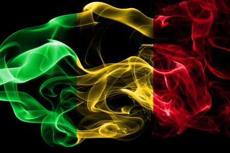 National flag of Mali made from colored smoke isolated on black background. Abstract silky wave background. Фото со стока