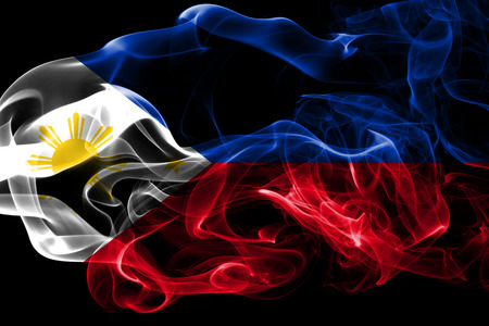National flag of Philipines made from colored smoke isolated on black background. Abstract silky wave background.