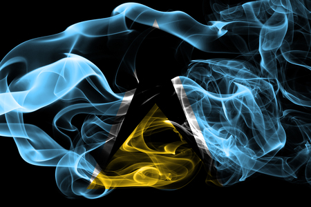 National flag of Saint Lucia made from colored smoke isolated on black background. Abstract silky wave background.
