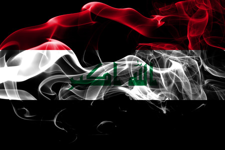 National flag of Iraq made from colored smoke isolated on black background. Abstract silky wave background.