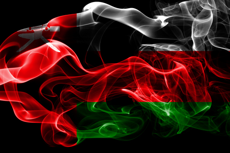 National flag of Oman made from colored smoke isolated on black background. Abstract silky wave background. Reklamní fotografie