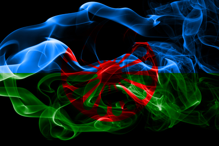 National flag of Gipsy made from colored smoke isolated on black background. Abstract silky wave background. Reklamní fotografie