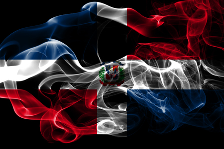National flag of Dominican Republic made from colored smoke isolated on black background. Abstract silky wave background.