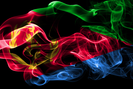 National flag of Eritrea made from colored smoke isolated on black background. Abstract silky wave background.
