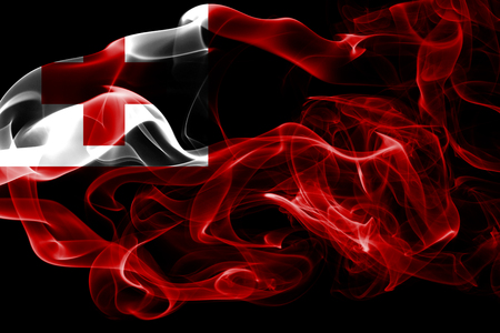 National flag of Tonga made from colored smoke isolated on black background. Abstract silky wave background.