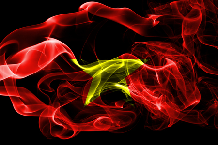 National flag of Vietnam made from colored smoke isolated on black background. Abstract silky wave background.