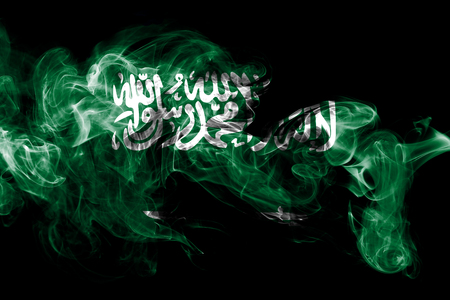 National flag of Saudi Arabia made from colored smoke isolated on black background. Abstract silky wave background.