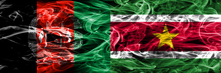 Afghanistan vs Suriname smoke flags placed side by side. Thick colored silky smoke flags of Afghani and Suriname