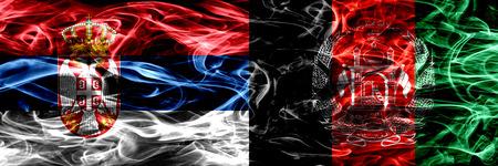 Serbia vs Afganistán, banderas de humo afganas colocadas una al lado de la otra. Banderas de humo sedoso de color espeso de Serbia y Afganistán, Afganistán