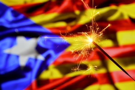 Close up of sparkler burning over Catalonia, Catalan flag. Holidays, celebration, party concept