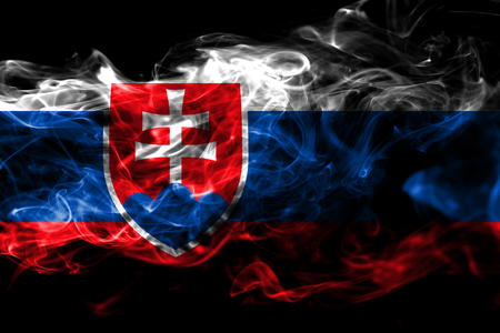 National flag of Slovakia made from colored smoke isolated on black background. Abstract silky wave background Фото со стока