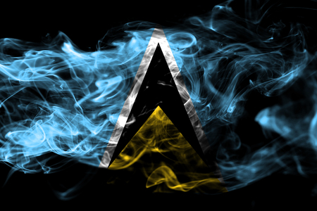 National flag of Saint Lucia made from colored smoke isolated on black background. Abstract silky wave background