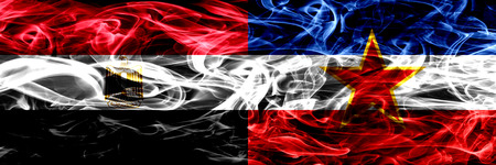 Egypt, Egyptian vs Yugoslavia smoke flags placed side by side. Thick abstract colored silky smoke flags Stock Photo