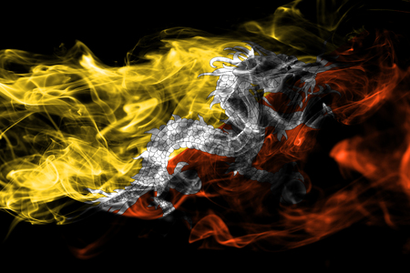 National flag of Bhutan made from colored smoke isolated on black background. Abstract silky wave background