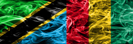Tanzania vs Guinea, Guinean smoke flags placed side by side. Thick colored silky smoke flags of Tanzanian and Guinea, Guinean 版權商用圖片