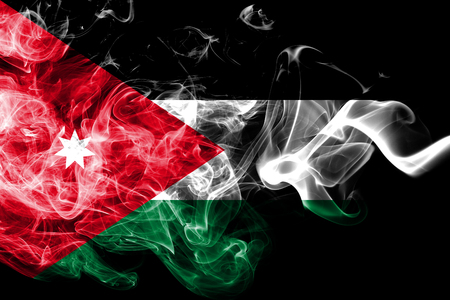 National flag of Jordan made from colored smoke isolated on black background. Abstract silky wave background.