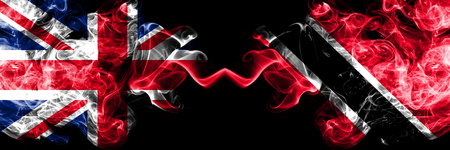 United Kingdom vs Trinidad and Tobago smoky mystic flags placed side by side. Thick colored silky smoke flags of Great Britain and Trinidad and Tobago. Stock Photo