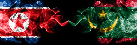 North Korea vs Mauritania, Mauritanian smoky mystic flags placed side by side. Thick colored silky smoke flags of North Korea and Mauritania, Mauritanian. Фото со стока